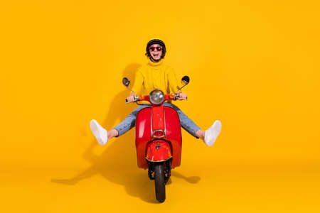 Photo portrait of funny girl driving red retro motorbike spreading legs isolated on vivid yellow colored background Archivio Fotografico
