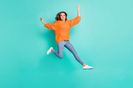 Full size photo of young pretty funky funny careless carefree girl with brown hair jumping isolated on turquoise color background 版權商用圖片