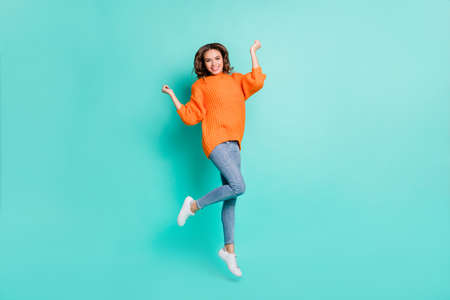 Full size photo of young happy positive excited girl jumping in victory wear orange pullover isolated on teal color background 版權商用圖片