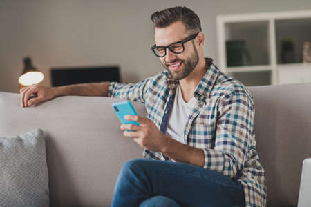 Photo of young cheerful man happy positive smile read browse internet cellphone chat type sms sit couch indoors