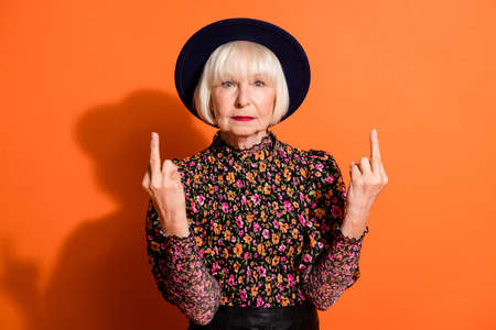 Photo portrait of bad rude granny showing fucking sign gesture in black hat isolated on vibrant orange background copyspace Фото со стока