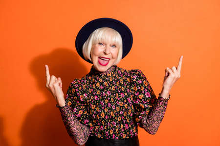 Photo portrait of crazy rude old lady demonstrating fucking sign gesture in stylish clothes isolated on bright orange background copyspace