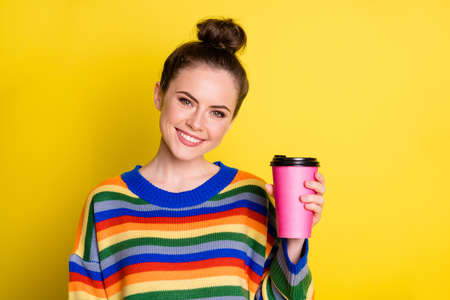 Photo of nice cute brunette girl hold cup wear rainbow sweater isolated on bright yellow color background