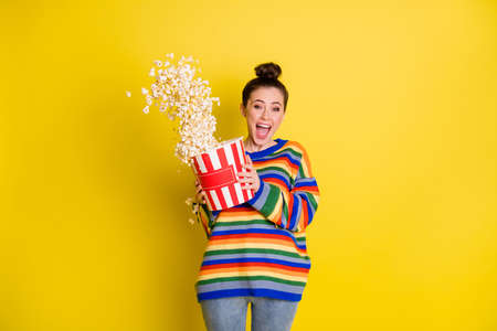 Photo of crazy rejoicing ecstatic hipster girl enjoying jokes from tv eating snack isolated over bright color yellow background
