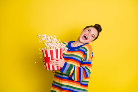 Photo of young crazy woman happy positive smile pop-corn fall air isolated over yellow color background Foto de archivo