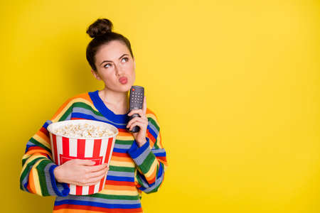 Photo of young attractive woman think hold remote control eat pop-corn look empty space isolated over yellow color background Foto de archivo