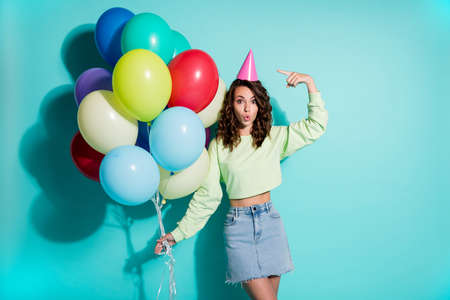 Photo of young lady hold bunch balloons direct finger hat wear cone headwear green sweater jeans short skirt isolated blue color background