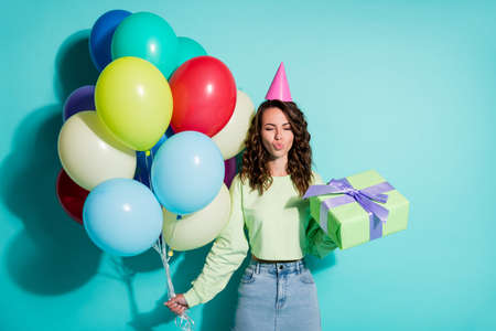 Photo of lady close eyes hold present balloons send air kiss wear cone cap green sweater jeans mini skirt isolated blue color background