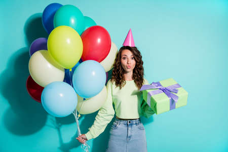 Photo of lady hold present many balloons send air kiss wear cone cap green sweater jeans short skirt isolated blue color background