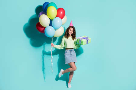 Photo of charming girl hold gift bunch balloons wear cone cap green sweater jeans mini skirt sneakers isolated blue color background