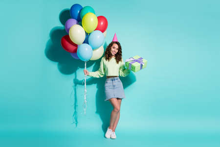 Photo of lovely girl hold present bunch balloons wear green sweater jeans mini skirt cone hat sneakers isolated blue color background