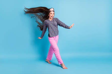Full length photo of charming young girl air blow long hairdo barefoot dreamy walk lovely bed wear mask dotted shirt pink pants pajamas sleepwear isolated blue color background