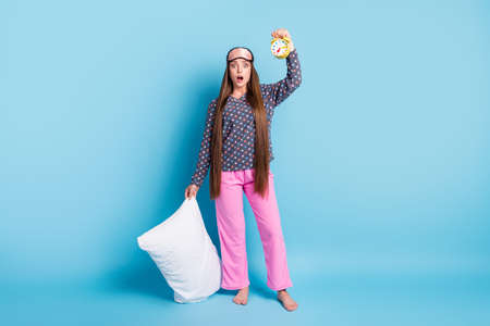 Full length photo of cute pretty teenager girl shocked open mouth hold clock pillow overslept university wear mask dotted shirt pink pants pajamas sleepwear isolated blue color background