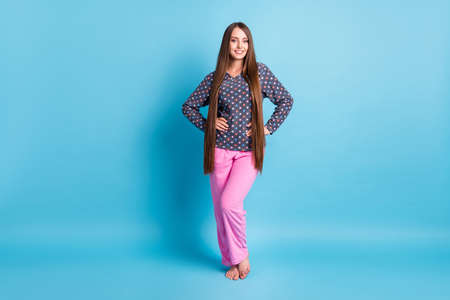 Full body size photo of cute charming young girl smiling hands hips barefoot prepare morning procedures wear dotted shirt pajamas sleepwear isolated bright blue color background Stock Photo