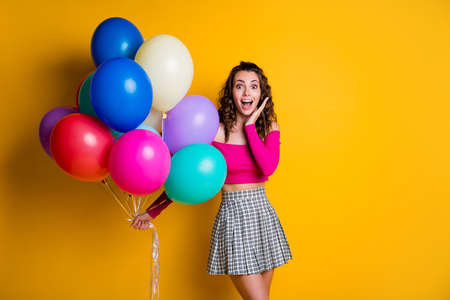 Portrait photo of surprised amazed girl holding colorful air balloons keeping hand neat face with opened mouth smiling wearing checkered skirt isolated on bright yellow color background Stock fotó