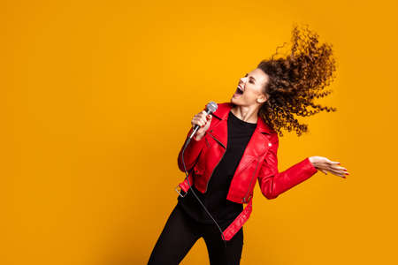 Portrait of pretty cheerful glad wavy-haired girl vocalist singing hit working on scene isolated on bright yellow color background Foto de archivo