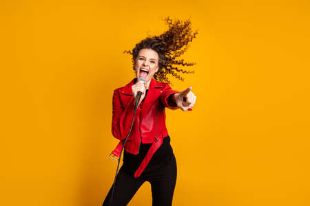 Portrait of attractive cheerful wavy-haired girl vocalist giving concert profession pointing isolated on bright yellow color background Banque d'images