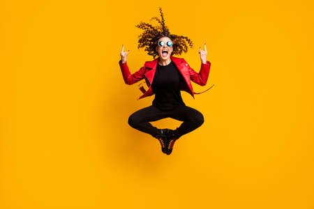 Full length body size view of cool crazy cheery wavy-haired girl jumping showing horn sign having fun isolated on bright yellow color background