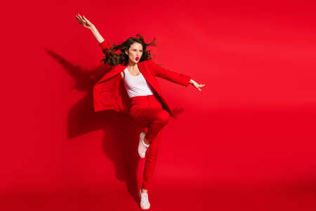 Full length photo of crazy stunning girl wind hairstyle lips raise hand wear blazer pants sneakers isolated red color background