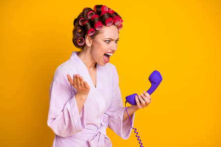 Profile side view portrait of pretty evil mad fury woman wearing curlers talking on phone yelling isolated bright yellow color background