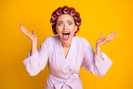 Close-up portrait of miserable desperate woman wearing curlers yelling claim bad mood isolated bright yellow color background
