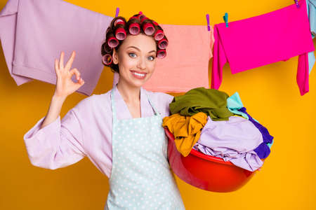 Portrait of attractive glamorous cheerful maid carrying hanging washed things showing ok-sign isolated bright orange color background