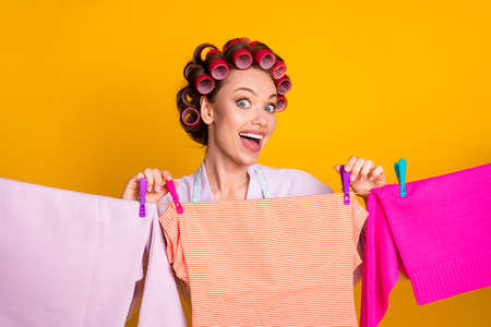 Close-up portrait of attractive glamorous cheerful maid hanging fresh washed things on rope isolated on bright orange color background
