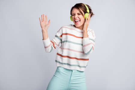 Photo of shiny pretty young woman dressed striped pullover headphones dancing singing arn hand side isolated grey color background