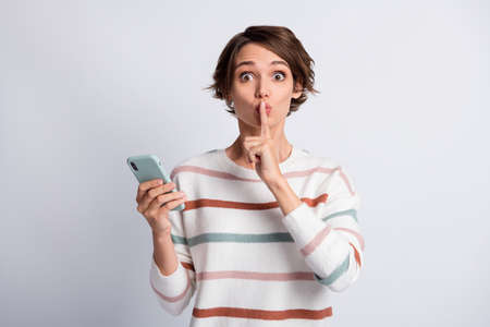 Photo of funny young lady wear striped sweater holding modern gadget ask not tell secrets isolated grey color background