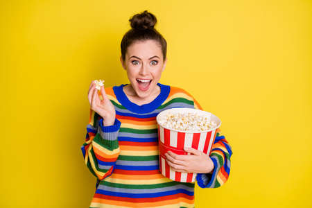 Photo of young girl watch film comedy eat pop-corn wear striped pullover isolated over yellow color background Foto de archivo