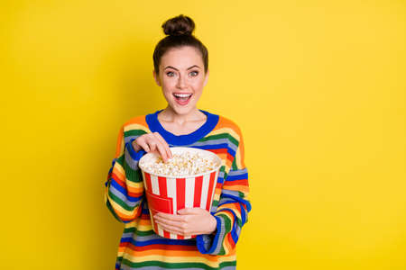 Photo of young attractive woman happy smile hold pop-corn box eat watch movie isolated over yellow color background Foto de archivo