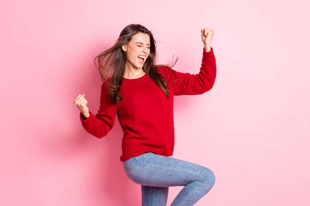 Photo of lovely girl closed eyes open mouth raise arms knee wear red sweater denim jeans isolated pink color background 免版税图像