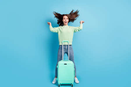 Finally holidays. Photo portrait of smiling happy girl standing near suitcase going to make a journey playing with hair isolated on vivid blue color background