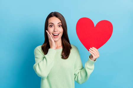 Photo portrait of amazed surprised girl showing red heart touching face smiling looking up isolated on vibrant blue color background