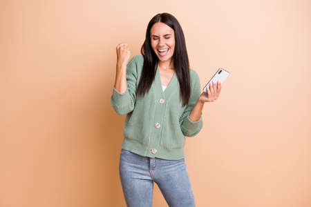 Photo of hooray girl hold telephone hand fist wear green sweater jeans isolated on peach color background
