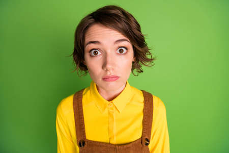 Photo of sad shocked girl speechless face look camera wear yellow shirt overall isolated green color background