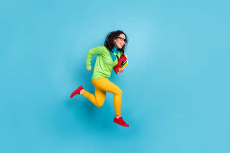 Full size profile side photo of brunette messy tails haired girl jump run empty space wear yellow pants isolated on blue color background