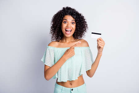 Photo portrait of excited woman holding plastic card in one hand pointing finger at it isolated on white colored background