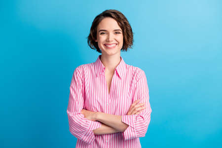 Photo portrait of curly charming pretty confident woman student dressed formal pink shirt arms crossed isolated blue color background
