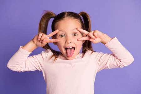Photo of playful cute small child make face show v-sign funky mood isolated on purple color background 写真素材