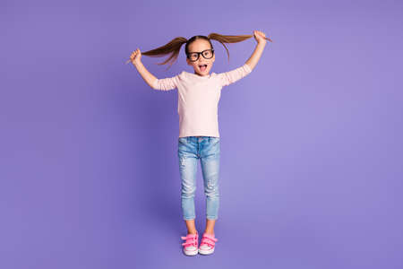 Full length photo of playful small girl hold hands pigtails wear spectacles sweatshirt isolated on violet color background 写真素材