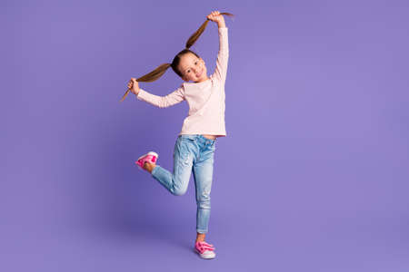 Full size photo of careless happy girl hold hands pigtails wear jeans sweater isolated on purple color background