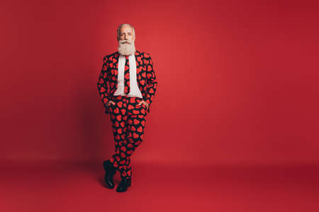 Photo of self-assured handsome pensioner man posing hands pockets wear heart print tux footwear isolated red background