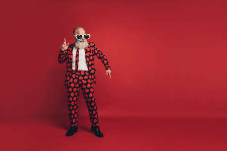 Photo of bearded disco man dance clubbing have fun wear vintage sunglass heart print tux isolated red background