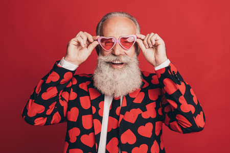 Photo of crazy funny retired gentleman look camera beaming smile wear heart sunglass tux isolated red background Stock fotó