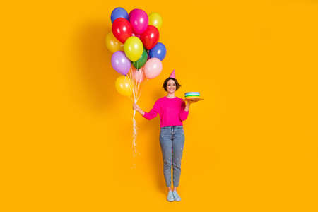 Full length photo of positive girl hold birthday cake hold balloons wear cone pullover isolated bright color background