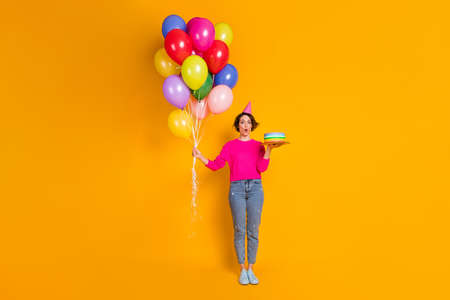 Full length photo of astonished girl hold birthday cake many balloons wear cone sweater isolated bright color background