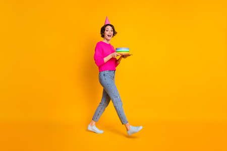 Full body photo of youngster lady hold birthday cake walk wear pullover cone hat jeans shoes isolated yellow color background
