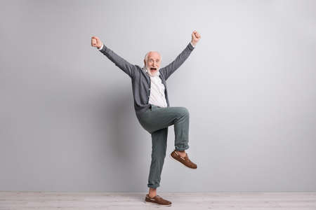 Full size photo of old funny impressed man dance hands fists wear dark sweater trousers boots isolated on grey wall