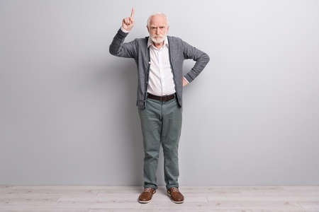 Full size photo of old sad man finger up wear dark sweater trousers boots isolated on grey wall